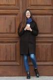 有华美的特长头发的年轻美丽的女孩在一条黑外套和蓝色围巾有一次性咖啡杯的获得乐趣反对wo 库存图片