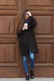 有华美的特长头发的年轻美丽的女孩在一条黑外套和蓝色围巾有一次性咖啡杯的获得乐趣反对wo 图库摄影