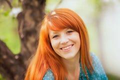 有华美的红色头发的愉快的妇女 免版税库存照片