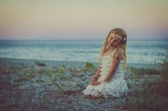 有单独坐在海滩的长的金发的可爱的女孩 免版税库存照片