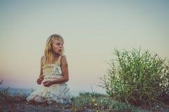 有单独坐在海滩的长的金发的可爱的女孩 库存照片