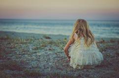 有单独坐在海滩的长的金发的女孩观看 免版税库存照片