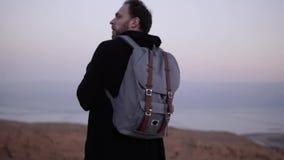 有单独站立在黄昏沙漠的背包的人 慢的行动 看日落天空的旅客 搜寻启发 股票视频
