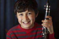 有单簧管的微笑的男孩 库存照片
