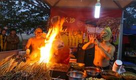 有卖在灯笼展示的面具的叫卖小贩烤肉,成都,瓷 图库摄影