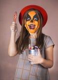 有南瓜的面孔绘画的俏丽的女孩 免版税库存图片
