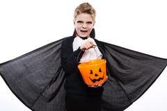 有南瓜篮子的男孩穿戴了象万圣夜党的吸血鬼 免版税库存图片