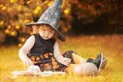 有南瓜nd spellbook的小巫婆 免版税库存照片