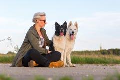 有博德牧羊犬和一只白德国牧羊犬的妇女 免版税库存照片
