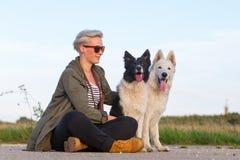 有博德牧羊犬和一只白德国牧羊犬的妇女 库存图片