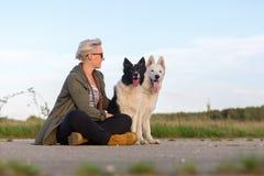 有博德牧羊犬和一只白德国牧羊犬的妇女 库存照片