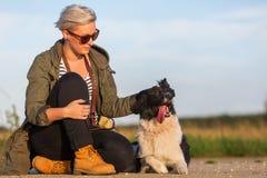 有博德牧羊犬的妇女坐路 免版税库存照片