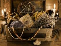 有占卜用的纸牌、裂缝合拢草本和水晶球的老巫婆箱子在桌上 库存照片