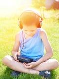 有卡型盒式录音机球员和耳机的小男孩 免版税库存照片