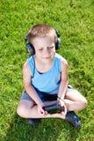 有卡型盒式录音机球员和耳机的小男孩 图库摄影