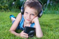 有卡型盒式录音机球员和耳机的小男孩 免版税库存图片