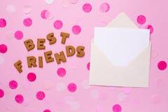 有卡片和五彩纸屑的信件曲奇饼最好的朋友在桃红色背景 库存图片