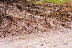 有卡车轨道的泥泞的村庄路 免版税库存照片