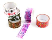 有印刷品的包装的磁带。礼品包装材料的修稿带。一套有一个装饰印刷品的色的包装磁带。 库存图片