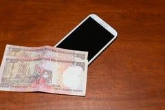 有印地安货币笔记的手机 免版税库存图片