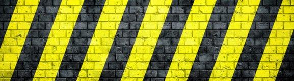 有危险或注意黑和黄色警告对角条纹的老和被风化的脏的砖墙构造背景横幅 库存照片