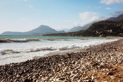 有卵石花纹的海滩日落,山景 黑山 免版税库存图片