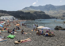 有卵石花纹的海滩的游人在Puerto de在大加那利岛的las Nieves, 免版税库存图片