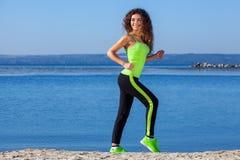 有卷发、浅绿色的运行在海滩的田径服和运动鞋的年轻运动员在夏天,早晨锻炼 库存照片