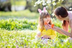 有卷发佩带的兔宝宝耳朵和夏天礼服的逗人喜爱的女孩获得与她的年轻母亲的乐趣,放松在庭院 免版税库存照片