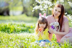 有卷发佩带的兔宝宝耳朵和夏天礼服的逗人喜爱的女孩获得与她的年轻母亲的乐趣,放松在庭院 库存图片