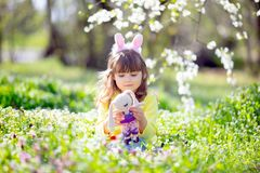 有卷发佩带的兔宝宝耳朵和夏天礼服的逗人喜爱的女孩获得乐趣在放松复活节彩蛋的狩猎期间在庭 库存照片