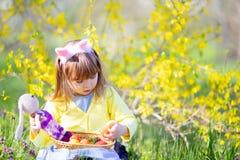 有卷发佩带的兔宝宝耳朵和夏天礼服的逗人喜爱的女孩获得乐趣在放松复活节彩蛋的狩猎期间在庭 图库摄影