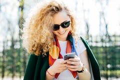 有卷发佩带的太阳镜和高尔夫球外套的美丽的妇女在她的手上拿着巧妙的电话浏览互联网的享用  免版税图库摄影