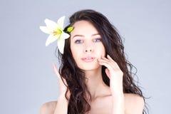 有卷发和百合的妇女在接触她的面颊的头发 夏威夷心情 库存图片