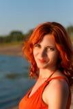 有卷发和美好的微笑的逗人喜爱的女孩在日落 库存图片
