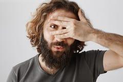 有卷发和胡子覆盖物的不耐烦的悦目东部人注视用手和偷看通过手指,称 免版税库存图片