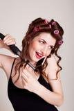 有卷发夹的女孩谈话在电话和做发型 库存图片