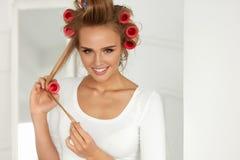 有卷发夹的,在健康卷曲的头发路辗美丽的妇女 免版税库存图片