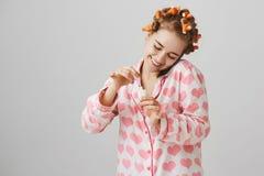 有卷发夹,佩带的可爱的睡衣的与心脏模板,绘的钉子逗人喜爱的愉快的年轻欧洲妇女和 库存照片