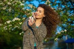 有卷发的一个可爱的少妇听到在您电话和微笑的音乐的 库存照片