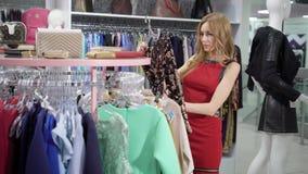有卷发的一个少妇在她的手上审查在一个时髦精品店的衣裳,她采取一件毛线衣 股票录像