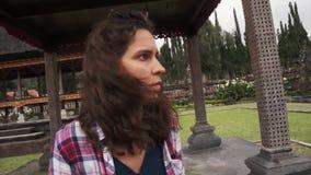 有卷发的可爱的女孩在树荫处在巴厘语公园坐夏日 股票录像