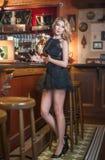 有卷发的可爱的白肤金发的妇女在站立近的高凳的典雅的短的鞋带礼服拿着一杯红葡萄酒 免版税库存照片