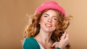 有卷发的女孩在一个桃红色帽子 免版税库存照片