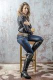 有卷发的女孩在一个黑衬衣、牛仔裤和高起动牛仔西部样式 库存照片