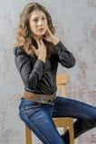 有卷发的女孩在一个黑衬衣、牛仔裤和高起动牛仔西部样式 免版税库存图片