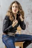 有卷发的女孩在一个黑衬衣、牛仔裤和高起动牛仔西部样式 免版税库存照片