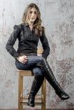 有卷发的女孩在一个黑衬衣、牛仔裤和高起动牛仔西部样式 库存图片