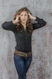 有卷发的女孩在一个黑衬衣、牛仔裤和高起动牛仔西部样式 免版税图库摄影
