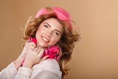 有卷发的女孩在桃红色帽子和围巾 免版税库存图片